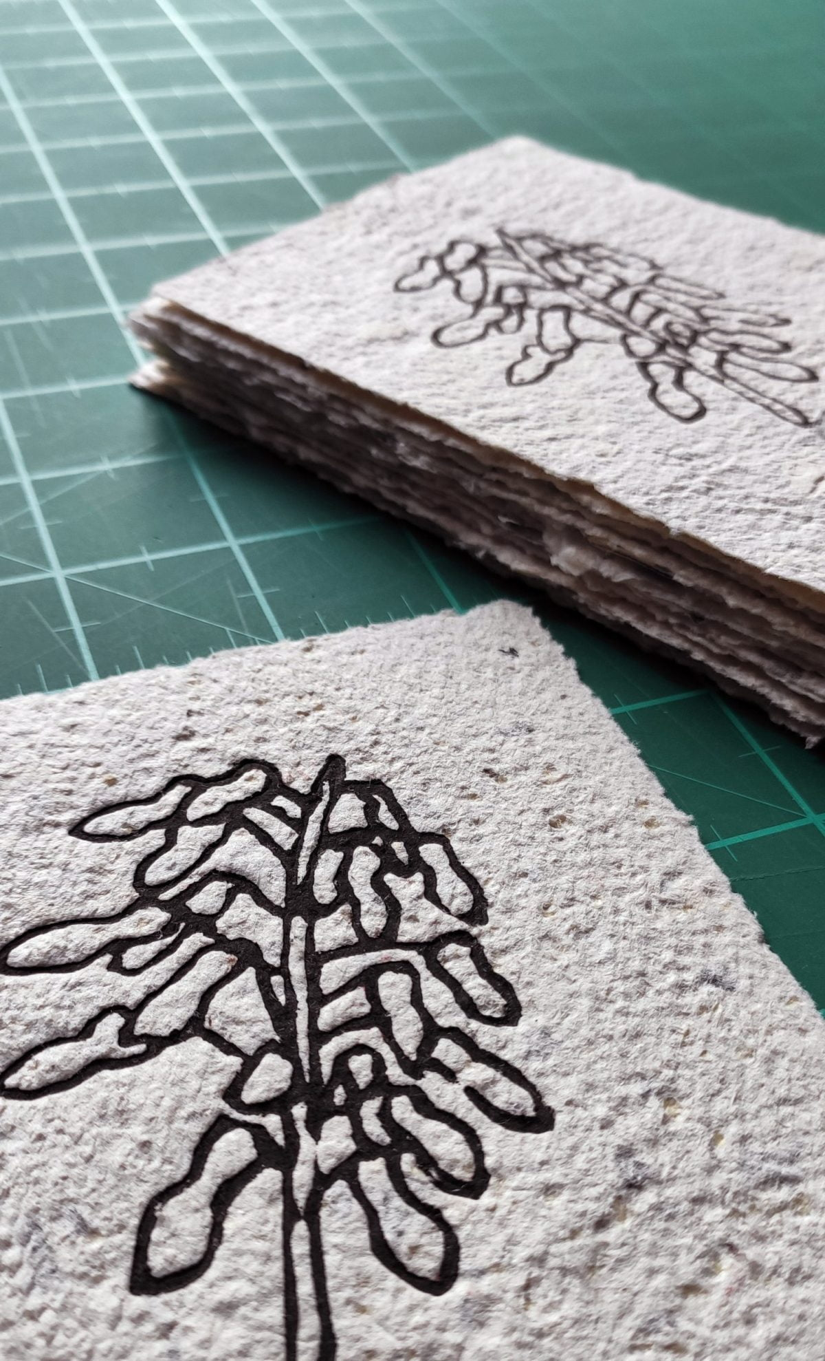 a linocut image of a flower on home-made paper