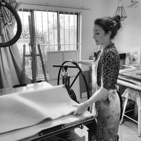 Claire Zinn using her etching press in her studio